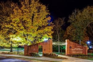 North Georgia college entrance sign at night time, lit up and surrounded in trees