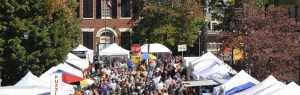 A photograph of people walking the dahlonega square at gold rush. Tents and vendors can be seen all throughout the square, with swarms of people in their fall clothes.