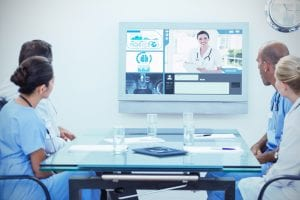 Group of male and female doctors sitting around a table, looking at a tv screen on the wall where they are in a video conference with another doctor