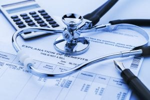 A bill of medical expenses with a calculator, pen and stethoscope laying on top
