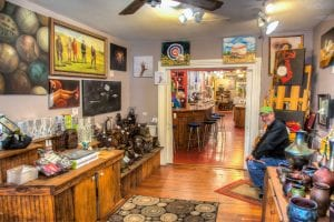 The interior of Bleu Art Gallery, with beautiful paintings on the wall, colorful vases on the counters, and a man sitting down smiling at the camera.