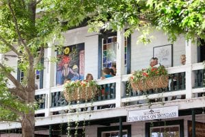 People sitting on the balcony of Bourbon Street Grill, located in the Dahlonega square.