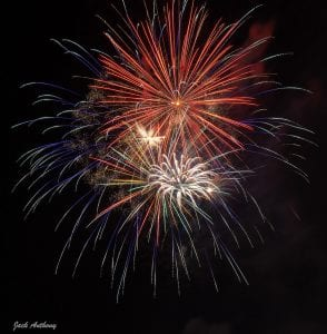 Fireworks bursting in the sky, a variety of colors including red, white and blue.
