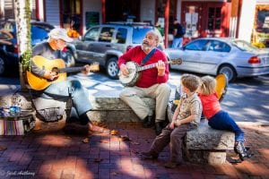 Two men playing the guitar on the dahlonega square, with two young children looking at them and listening